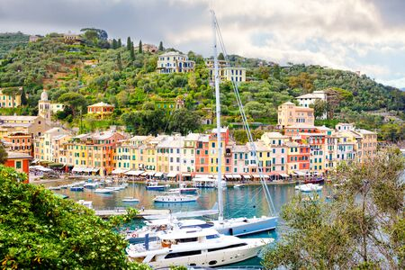 Beautiful small village Portofino with colorfull houses, luxury boats and yachts in little bay harbor. Liguria, Italy. On warm brigth summer day