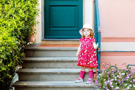 Portrait of beautiful little gorgeus lovely toddler girl in pink summer look clothes, fashion dress, knee socks and hat. Happy healthy baby child posing infront of colorful house.
