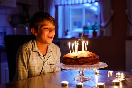 Adorable happy blond little kid boy celebrating his birthday. Child blowing candles on homemade baked cake, indoor. Birthday party for school children, family celebration 스톡 콘텐츠