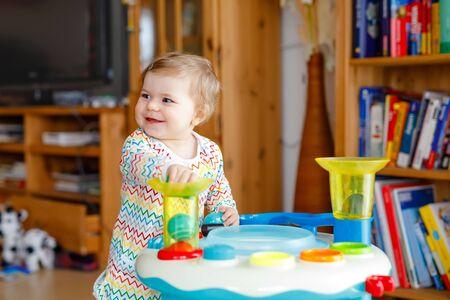 Fröhliches, fröhliches Baby, das zu Hause mit verschiedenen bunten Spielsachen spielt. Entzückendes gesundes Kleinkind, das Spaß beim Spielen allein hat. Aktive Freizeit drinnen, Kindergarten oder Kindergarten.