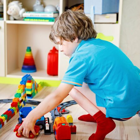 kid boy playing with colorful plastic blocks and creating train station. Child having fun with building railway toys during coronavirus quarantine staying at home. Shelter in place, lockdown concept.