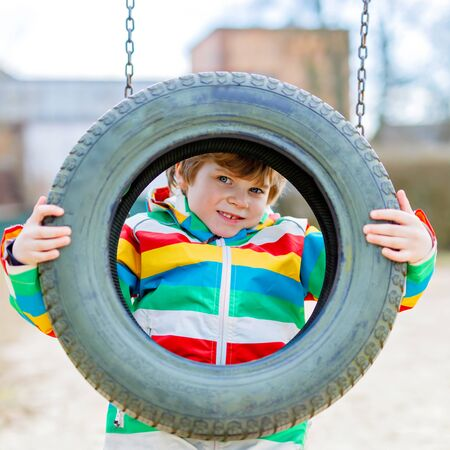 Funny kid boy having fun with chain swing on outdoor playground Banque d'images - 144162662