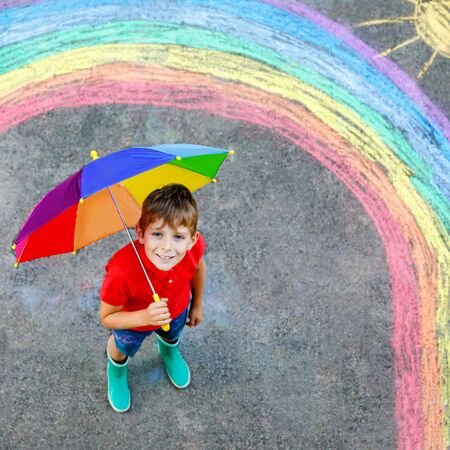 Happy kid boy with rainbow painted with colorful chalks on ground during pandemic coronavirus quarantine. Children painting rainbows along with the words Lets all be well 版權商用圖片