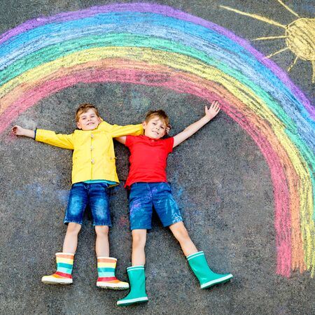 two school kids boys with rainbow painted with colorful chalks on ground during pandemic coronavirus quarantine. Children painting rainbows along with the words Lets all be well.