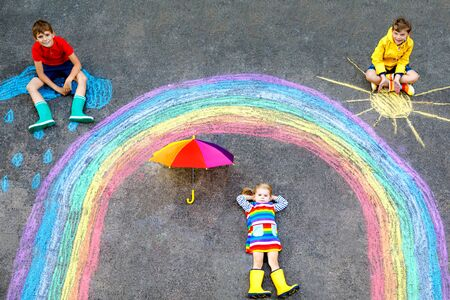 three kids, two school kids boys and toddler girl with rainbow painted with colorful chalks during pandemic coronavirus quarantine. Children painting rainbows along with the words Lets all be well.