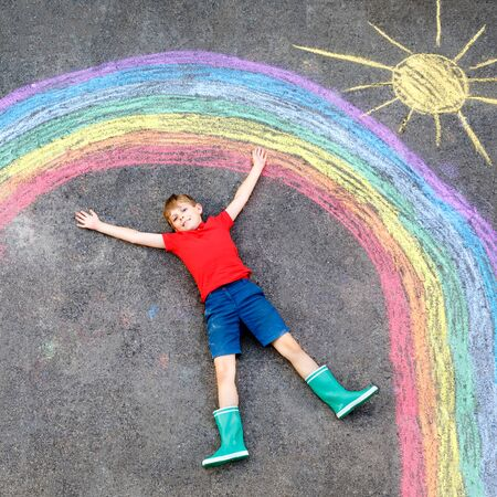Happy kid boy with rainbow painted with colorful chalks on ground during pandemic coronavirus quarantine. Children painting rainbows along with the words Lets all be well.