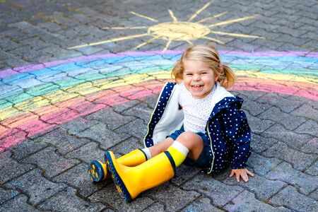 Happy little toddler girl in rubber boots with rainbow painted with colorful chalks on ground during pandemic coronavirus quarantine. Children painting rainbows along with the words Lets all be well