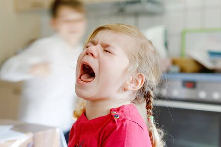 Cute upset unhappy toddler girl crying. Angry emotional child shouting. Portrait of kid with tears. Foto de archivo