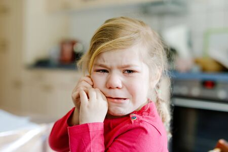 Cute upset unhappy toddler girl crying. Angry emotional child shouting. Portrait of kid with tears.