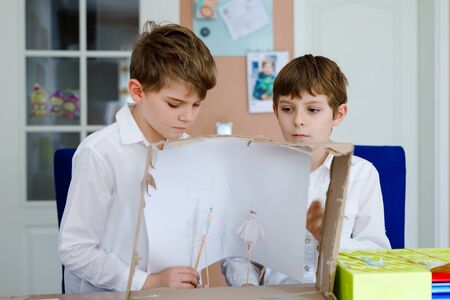 Two little school kids boy making paper doll theatre. Happy children and friends creating figures and performing stage play during quarantine time at home. Active creative siblings staying at home. Foto de archivo