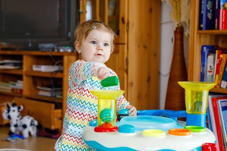 Happy joyful baby girl playing with different colorful toys at home. Adorable healthy toddler child having fun with playing alone. Active leisure indoors, nursery or playschool.