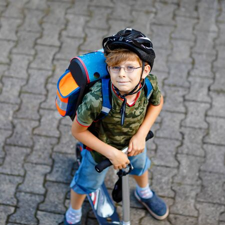 Active school kid boy in safety helmet riding with his scooter in the city with backpack on sunny day. Happy child in colorful clothes biking on way to school. Safe way for kids outdoors to school.