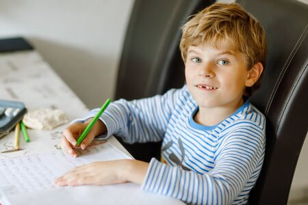 Portrait of cute healthy happy school kid boy at home making homework. Little child writing with colorful pencils, indoors. Elementary school and education. Kid learning writing letters and numbers