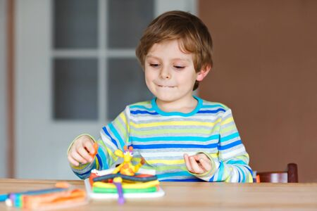 Smiling preschool kid boy having fun with dough, colorful modeling compound clay. Creative leisure with children. during corona virus quarantine staying at home. Shelter in place, lockdown concept,
