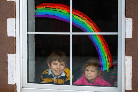 Two kids, school boy and toddler girl with rainbow painted with colorful window color during pandemic coronavirus quarantine. Children painting rainbows with the words Lets all be well