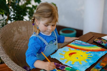 little toddler girl painting rainbow and sun with water colors during pandemic coronavirus quarantine disease. Children painting rainbows around the world with the words Lets all be well. Happy child Stock Photo