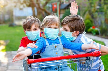 three kids, little toddler girl and two kid boys in medical mask as protection against pandemic coronavirus disease. Children with shopping cart using protective equipment as fight against covid 19.