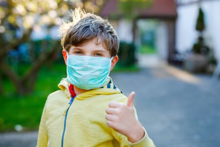 Adorable kid boy in medical mask as protection against pandemic coronavirus quarantine disease. School child using protective equipment as fight against covid 19.