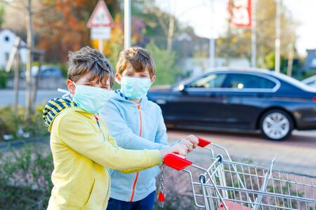Two kids boys in medical mask as protection against pandemic coronavirus disease. Children using protective equipment against covid 19 and going for shopping in supermarket with cart trolley.