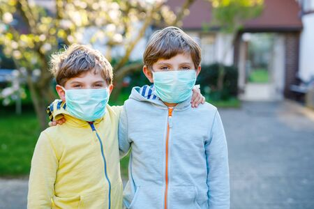 Two kids boys in medical mask as protection against pandemic coronavirus disease. Children, lovely siblings and best friends using protective equipment as fight against covid 19.
