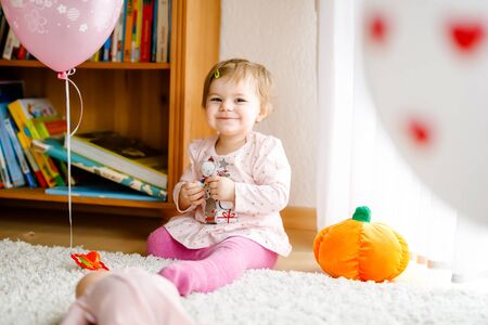 Lovely cute beautiful little baby girl playing with educational toys at home or nursery. Happy healthy child having fun with colorful different toys. Toddler learning different skills Foto de archivo