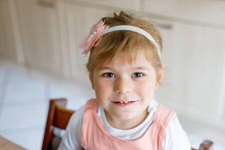 Portrait d'une adorable petite fille mignonne de trois ans. Beau bébé aux cheveux blonds regardant et souriant à la caméra. Heureux enfant en bonne santé.