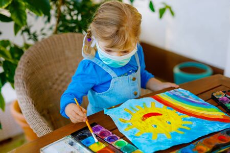 little toddler girl in medical mask painting rainbow with water colors during pandemic coronavirus quarantine disease. Children painting rainbows around the world with the words Lets all be well.