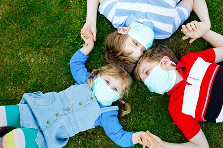 three kids, little toddler girl and two kid boys in medical mask as protection against pandemic coronavirus disease. Children, lovely siblings using protective equipment as fight against covid 19.