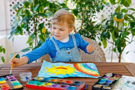 little toddler girl painting rainbow and sun with water colors during pandemic coronavirus quarantine disease. Children painting rainbows around the world with the words Lets all be well. Happy child Reklamní fotografie