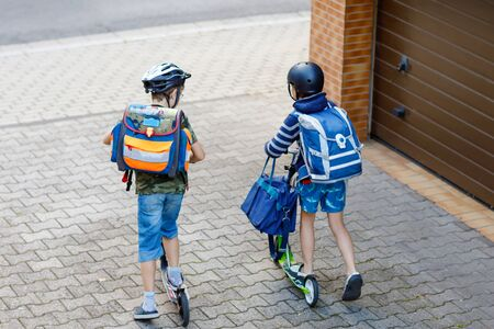 Two school kid boys in safety helmet riding with scooter in the city with backpack on sunny day. Happy children in colorful clothes biking on way to school. Unrecognizable faces from above back