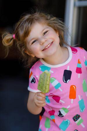 Cute funny toddler girl eating fruit ice cream at home. Happy healthy baby child smiling and tasting kiwi sweet ice-cream. Lovely kid enjoying dessert. Reklamní fotografie