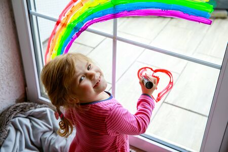 Adoralbe little toddler girl with rainbow painted with colorful window color during pandemic coronavirus quarantine. Child painting rainbows around the world with the words Lets all be well. Reklamní fotografie
