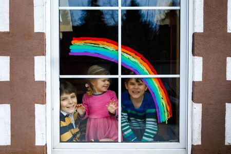 Three kids, two school kids boys and toddler girl with rainbow painted with colorful window color during pandemic coronavirus quarantine. Children painting rainbows with the words Lets all be well.