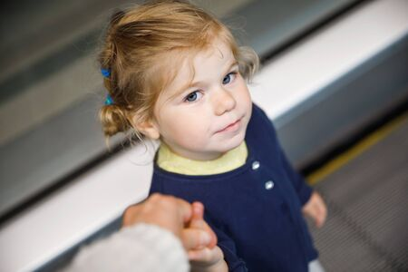 Adorable little toddler girl at the airport. Lovely child walking to the gate and going on family vacations by plane. Positive happy child.
