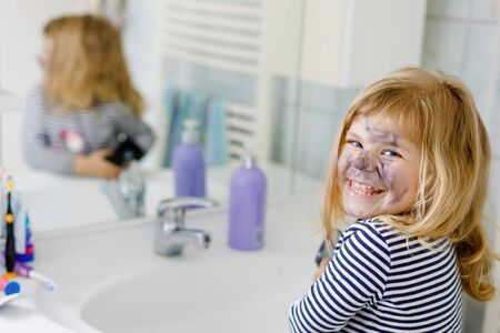 Funny little toddler girl using mothers make up and painting face with eye shadows. Happy baby child making experiments with cosmetics of mother. Kid around