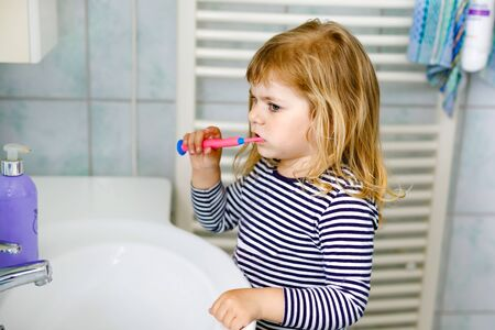 Cute little girl with a toothbrush in her hand cleans her teeth and smiles. Funny happy healthy child learning morning routing with washing face and cleaning teeth Reklamní fotografie