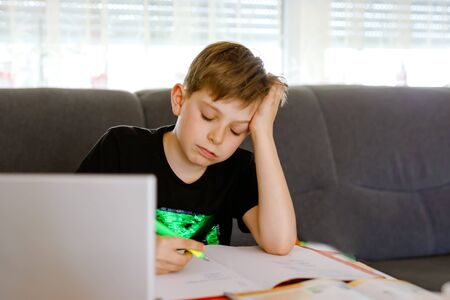Upset school kid boy making homework during quarantine time from corona pandemic disease. Frustrated sad boy learning staying at home with video via laptop. Homeschooling concept Reklamní fotografie