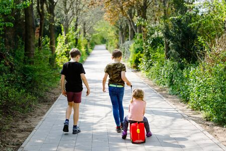 three kids, little toddler girl and two kid boys walking in park pandemic coronavirus disease. Children, lovely siblings playing together as family, using toy car suitcase on wheels Reklamní fotografie