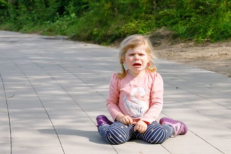 Cute upset unhappy toddler girl crying. Angry emotional child shouting. Portrait of kid with tears. Girl sitting on ground at crying Reklamní fotografie