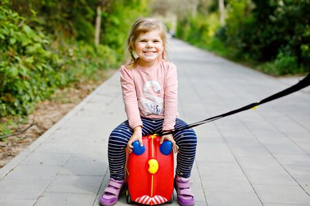 little toddler girl walking in park pandemic coronavirus disease. Cute adorable child playing with toy car suitcase on wheels