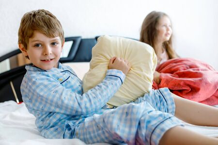 Two happy kids in pajamas celebrating pajama party. Preschool and school boy and girl having fun together. Children playing together in bed. Making pillow fight.