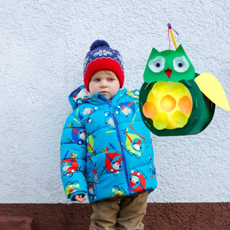 Little kid boy holding selfmade lanterns for a Halloween or St. Martin procession. Beautiful healthy cute child happy about children and family parade in kindergarten. German tradition Martinsumzug Reklamní fotografie