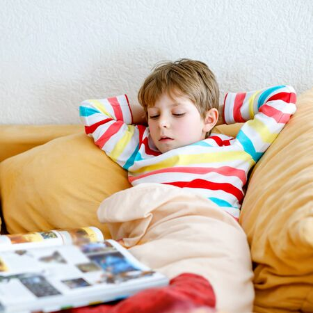 Little blonde school kid boy with glasses reading a book at home. Child interested in reading magazine for kids. Leisure for kids, building skills and education concept Фото со стока
