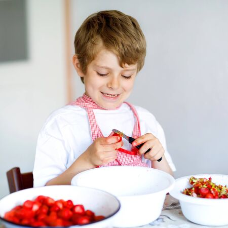 Little blond kid boy helping and making strawberry jam in summer. Funny child cleaning berries and preparing for cooking jam. Kid eating ripe strawberries in domestic kitchen
