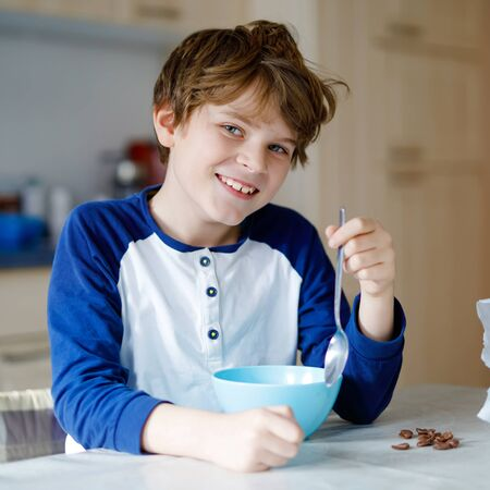 Happy little blond kid boy eating cereals for breakfast or lunch. Healthy eating for children. Child in colorful pajama having breakfast with milk and muesli.