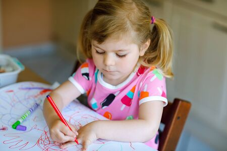 little toddler girl painting with different colorful pens and felt pencils during pandemic coronavirus quarantine disease. Child alone at home, closed nursery