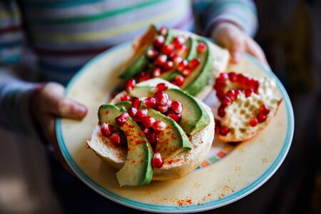 Healthy homemade sandwich with avocado and pomegranate for breakfast. Vegan or vegetarian meal.