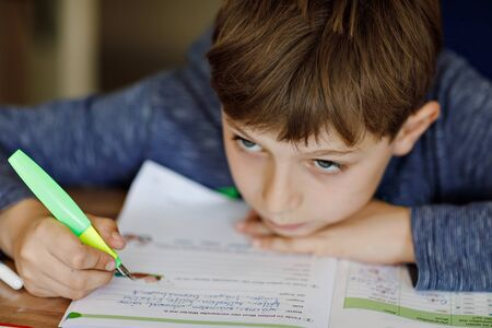Upset school kid boy making homework during quarantine time from corona pandemic disease. Tired and sad boy frustrating staying at home. Homeschooling concept