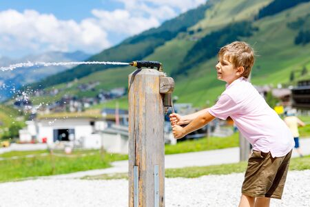 Little school kid boy playing with water pump on hot summer day. Mountains in Austria on background. Outdoors playground for children