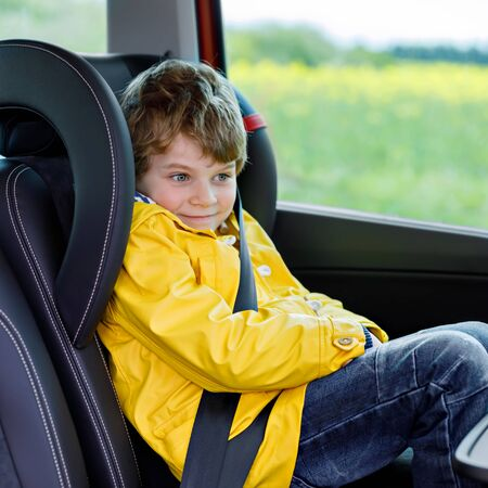 Cute preschool kid boy sitting in car in yellow rain coat. Little school child in safety car seat with belt enjoying trip and jorney. Safe travel with kids and traffic laws concept.